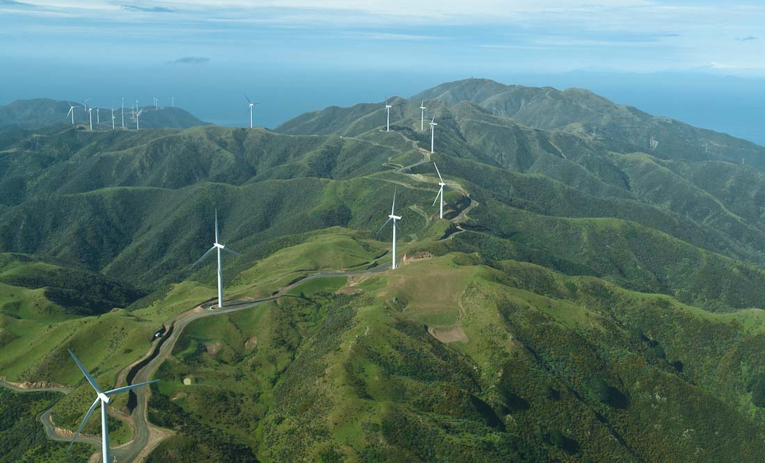 A long line of windmills spaced out over rolling hills in New Zealand